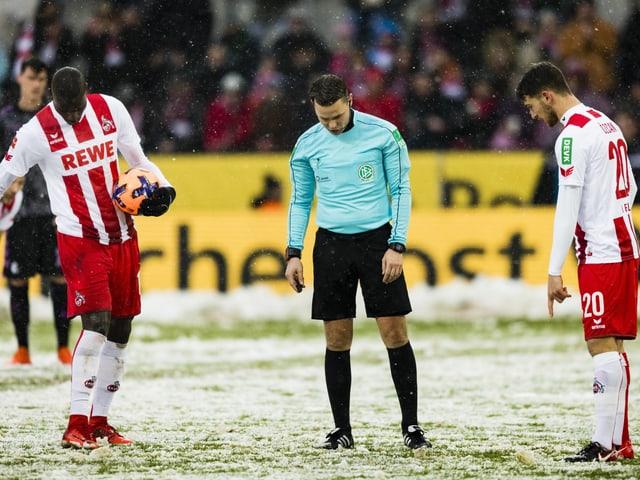 Kölner Spieler und der Schiedsrichter suchen den Penaltypunkt
