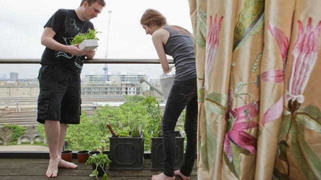 Zwei junge Leute giessen Pflanzen auf einem Balkon.