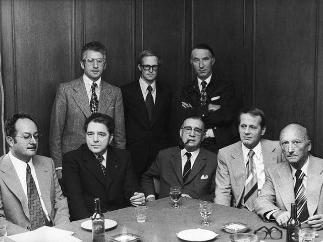 eine schwarz-weiss Fotografie von Männern an einem runden Tisch