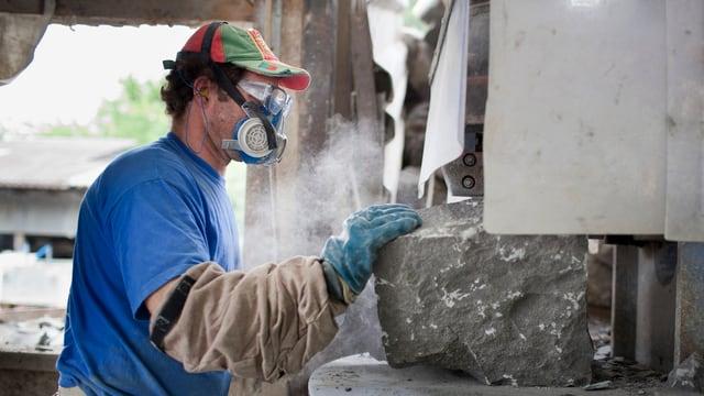 Ein Arbeiter in einem Steinbruch-Betrieb. Er trägt Mundschutz und eine Mütze mit der portugiesischen Flagge.