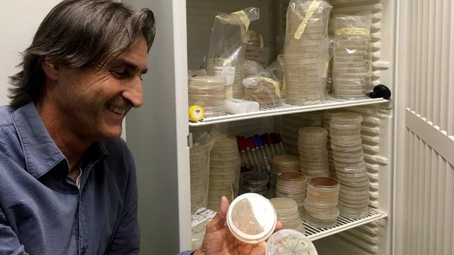 Ein Mann mit dunklen Haaren, blauem Hemd steht vor einem Kühlschrank und hält zwei Petrischalten in den Händen.