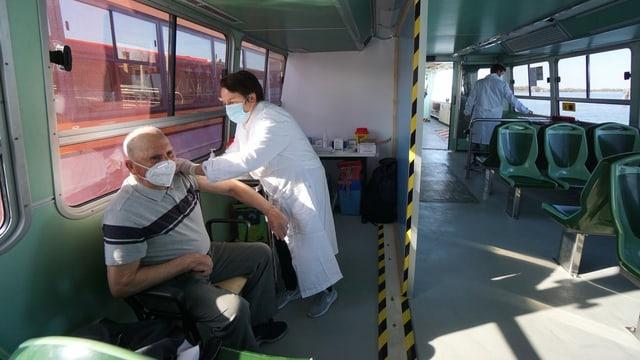 Ein älterer Mann im T-Shirt bekommt von einem Arzt im weissen Kittel auf einem Boot die Corona-Impfung.