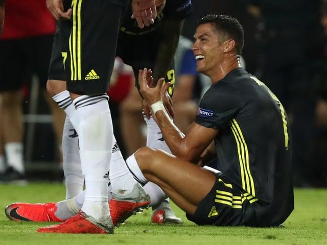 Christian Ronaldo sitzt händeringend auf dem Rasen.