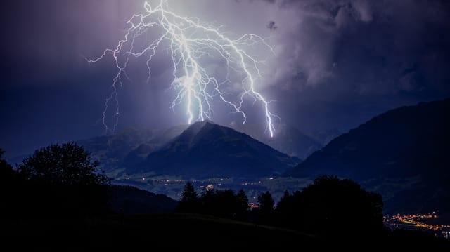 Mehrere Blitze schlagen gleichzeitig in die Bergkrete.