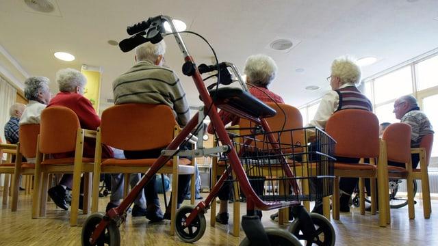 Rollator vor sitzenden Senioren.