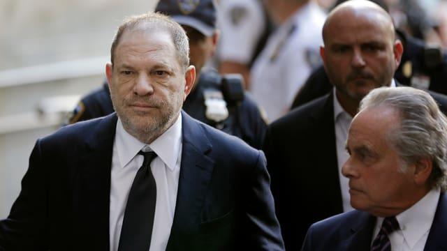 Harvey Weinstein trägt einen dunkelblauen Anzug und läuft mit ernster Miene ins Gesicht.