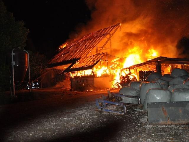 Stall brennt lichterloh, Aufnahme aus der Ferne mit Siloballen im Vordergrund.