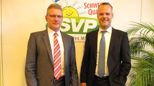Baudirektor Heinz Tännler und Bildungsdirektor Stephan Schleiss vor einem SVP-Plakat.