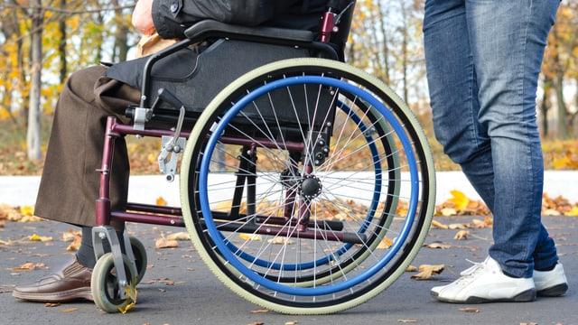 Eine Person schiebt eine andere Person im Rollstuhl.