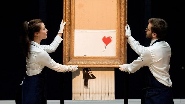 Eine Frau und ein Mann halten einen Bilderrahmen, in dem ein Bild geschreddert wird.