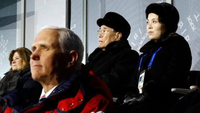 Pence und die Schwester sitzen hintereinander in zwei Reihen bei der Eröffnungsfeier der Olympischen Spiele.