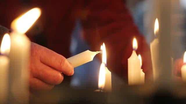 Besucher einer Kirche zündet eine Kerze an, andere Kerzen brennen bereits.