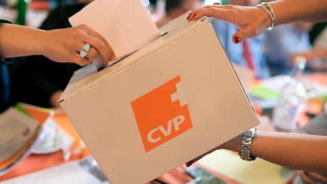 Eine Hand steckt einen Wahlzettel in eine Urne mit CVP-Logo