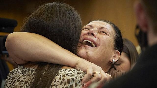 Eine Frau, die erleichtert eine andere junge Frau umarmt und dabei weint.
