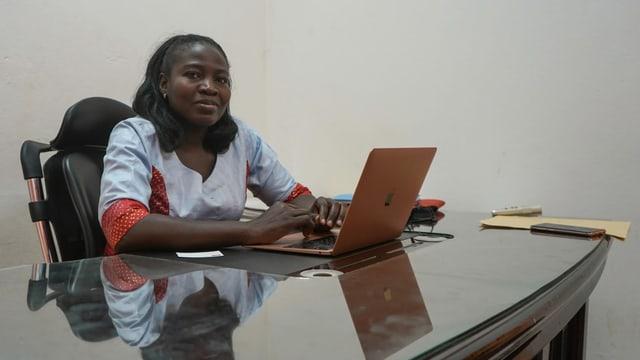 Dunkle Frau sitzt an einem Laptop.