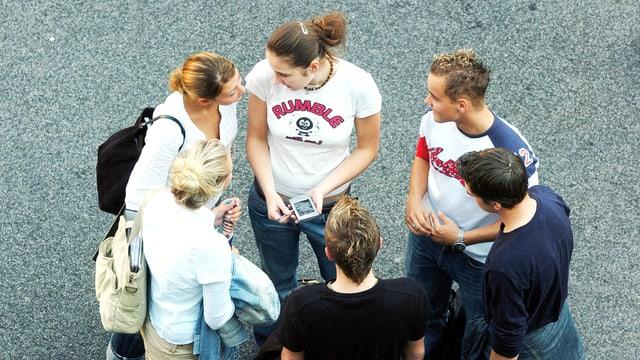 Eine Gruppe aus Mädchen und Jungs steht in einem Kreis und ist am Tratschen.