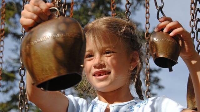 Ein kleines Mädchen bringt zwei kleine Glocken zum Klingen.