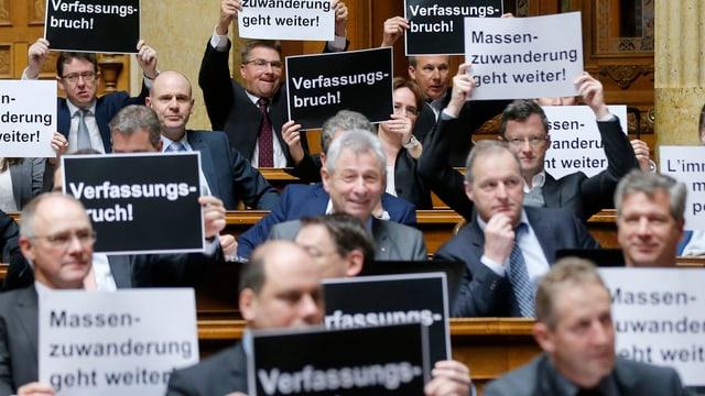 """Männer in Anzügen halten Plakate in die Luft. Darauf steht """"Verfassungsbruch"""""""
