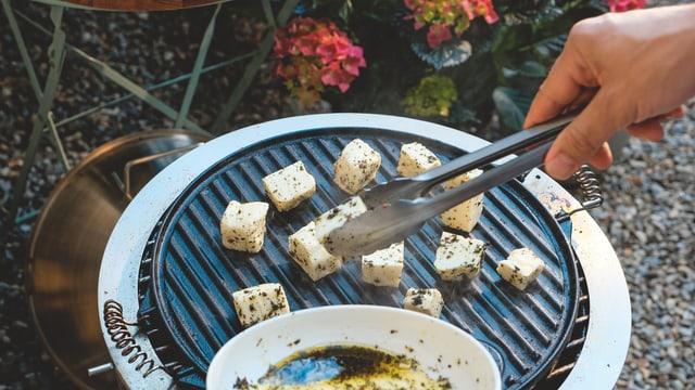 Grillkäse in Stücken auf einer Grillplatte.