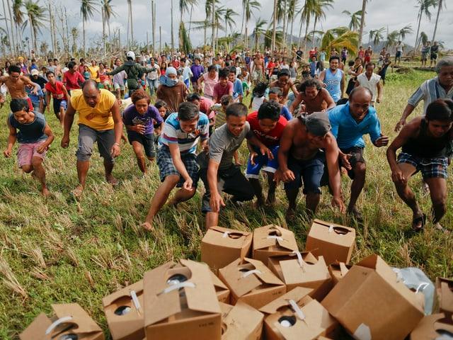 Unzählige Menschen springen auf ausgeladene Hilfsgüter in Kartons zu.