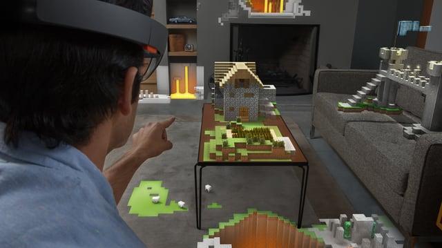 Mann mit HoloLens-Brille zeigt auf einen Tisch. Dort sieht man ein Haus aus Minecraft Bauklötzen.