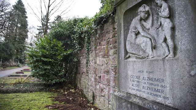 Blick auf ein Grabmahl an einer Steinmauer.
