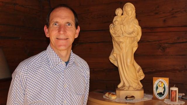 Pfarrer Brunner steht vor einer Maria-Statue.
