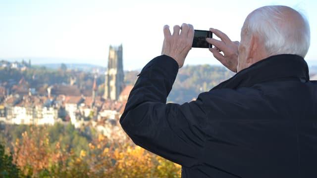 Ein Mann fotografiert mit seinem Smartphone das Panorama einer Stadt.