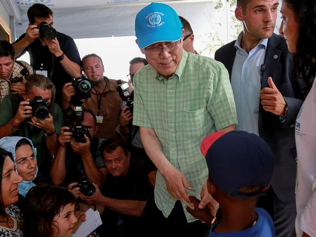 Ban Ki-moon mit cooler blauer UNO-Schirmmütze schüttelt Flüchtlingskindern die Hände.