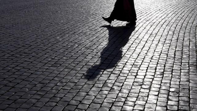 Mönch und sein Schatten auf einem Platz
