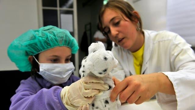 Eine Ärztin «behandelt» mit einem Mädchen mit Mundschutz und Gummihandschuhen ein Plüschtier.