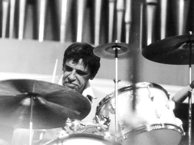Ein dunkelhaariger Mann sitzt hinger einem Schlagzeug und spielt.