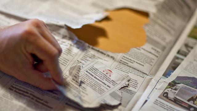 Eine Hand reisst ein Stelleninserat aus der Zeitung.