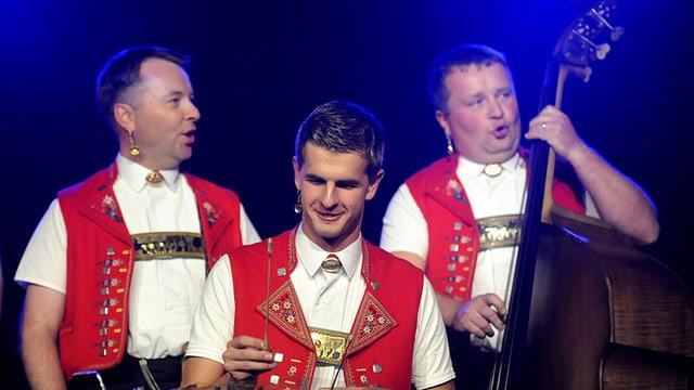 Nicolas Senn sitzend am Hackbrett begleitet von zwei weiteren Musikern in Appenzeller Sennentracht.