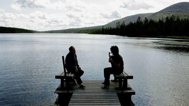 Zwei Männer sitzen auf einem Steg an einem See.