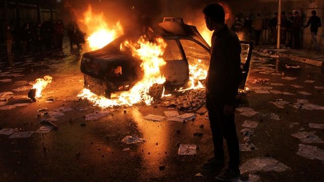 Protestierender vor einem brennenden Auto.