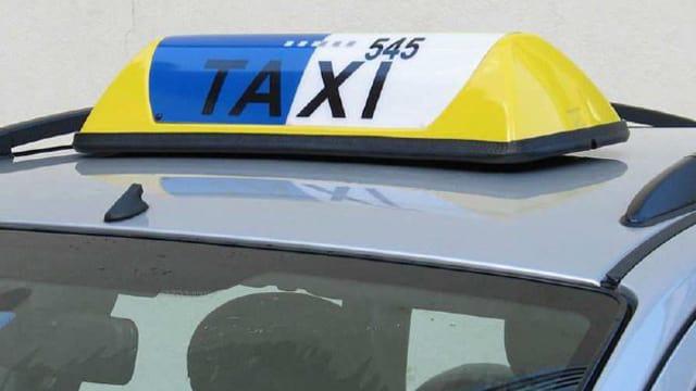 EIn Autodach mit einer gelben Taxilampe und mit einem blauweissen Signet drauf.