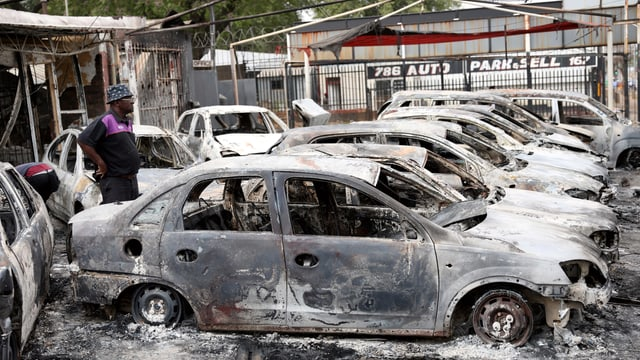Mann vor verbrannten Autos.