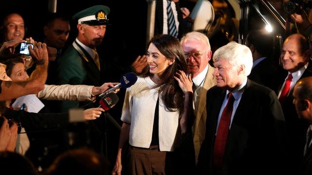 Presserummel rund um Amal Clooney. Diverse Reporter strecken ihr Mikrophone ins Gesicht.