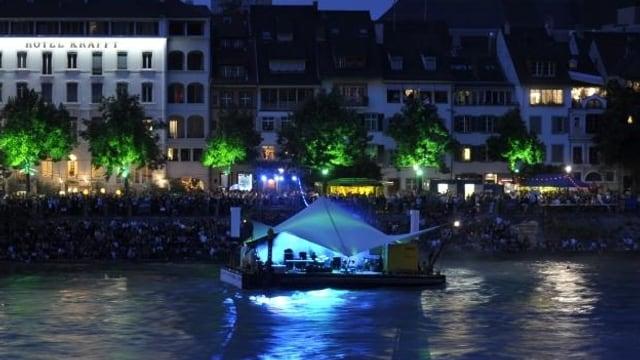 Das bläulich beleuchtete Floss schaukelt auf dem Rhein, von der Grossbasler Seite her fotografiert.