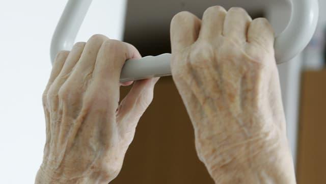 Symbolbild: Zwei Hände eines alten Menschen halten den Griff über dem Spitalbett.