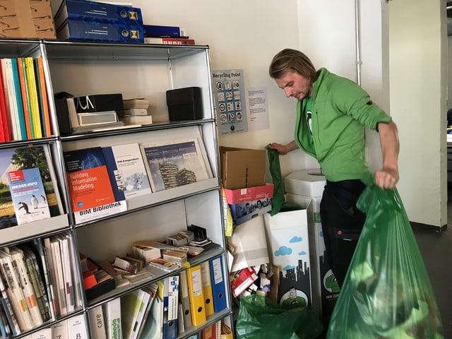 Mann mit grünen Sammelsack in einem Büro.