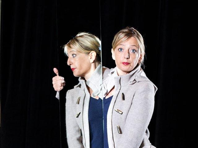 Brigitte Rosset neben einem Spiegel, ins Publikum schauend. Ihr Spiegelbild ist im Profil zu sehen.