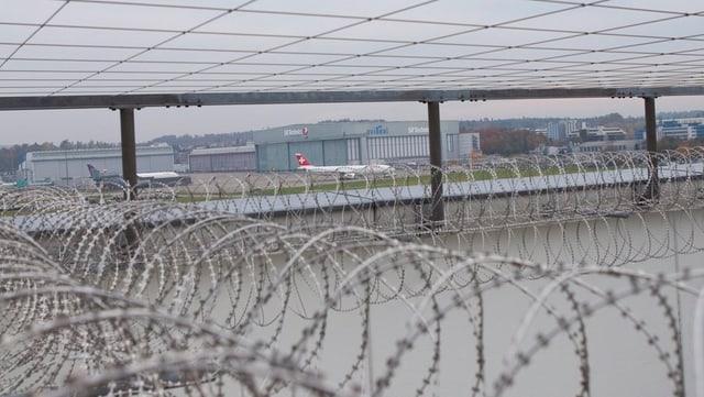 Stacheldraht am Ausschaffungsgefängnis Zürich, dahinter ein Swiss-Flugzeug.
