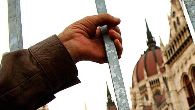 Eine Hand greift in die Gitter vor dem ungarischen Parlament in Budapest.
