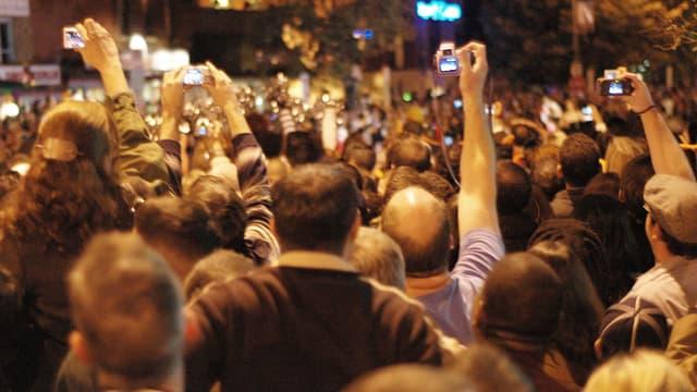 Menschenmenge hält Kameras in die Luft