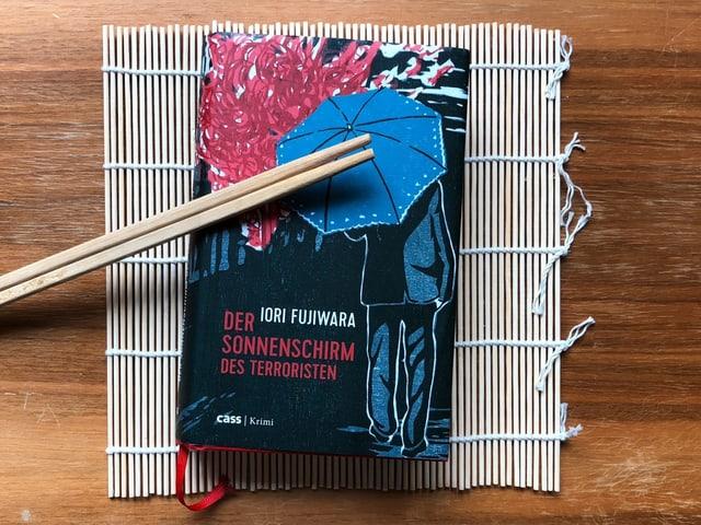 «Der Sonnenschirm des Terroristen» liegt auf einer Shusi-Roll-Matte. Stäbchen quer drüber.