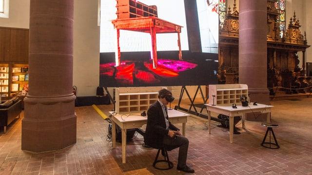 Ein Mann sitzt mit Virtual-Reality-Brille im Museum.