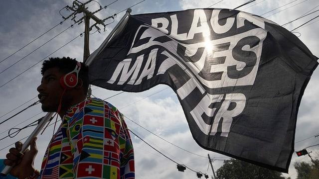 Ein «Black Lives Matter»-Aktivist in Virginia (USA) trägt eine Fahne der Bewegung.