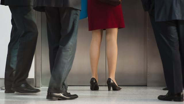 Eine Frau wartet an einem Lift, hinter ihr warten vier Männer. Sichtbar sind nur die Beine der fünf Personen. (keystone)